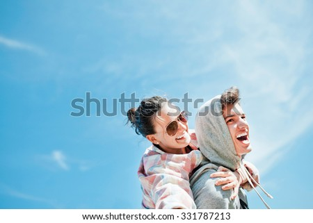 Happy loving couple. Happy young man piggybacking his girlfriend. Cheerful laughing hipsters on blue sky background with copy space - stock photo