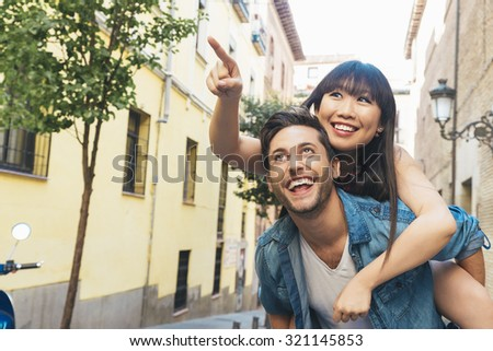 Happy loving couple. Happy young man piggybacking his girlfriend while pointing out at front - stock photo