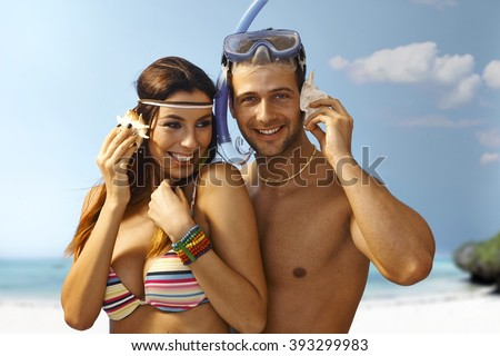 Happy loving couple hugging on the beach, listening to murmur of sea in seashell, smiling. - stock photo