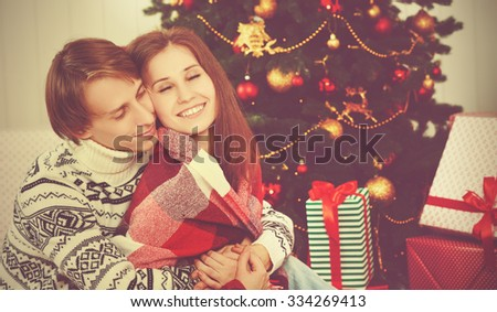 happy loving couple in an embrace warmed at Christmas tree  - stock photo