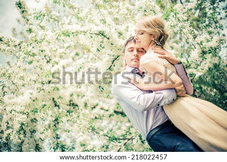 happy loving couple in the summer park with apple trees  - stock photo