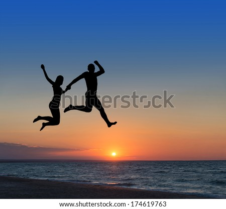 happy loving couple jumping highly in the sky at beach resort - stock photo