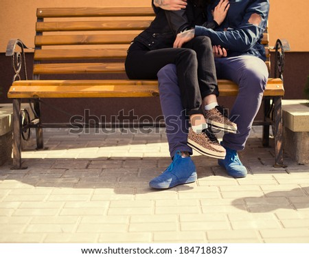 Happy loving couple on a bench in the summer - stock photo
