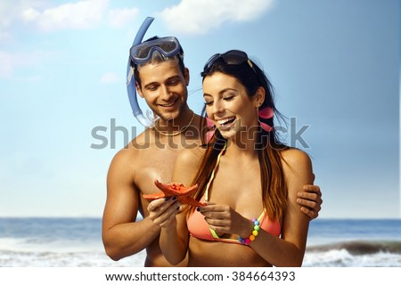 Happy loving couple on beach holding sea star, smiling. Man scuba-diving. - stock photo