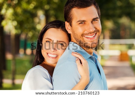 Happy loving couple. Portrait of beautiful young couple bonding to each other and smiling while both standing outdoors  - stock photo
