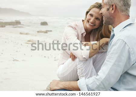 Happy loving couple sitting on beach - stock photo
