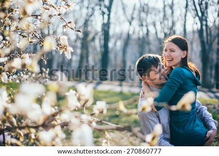 Happy loving couple spending great time in park. Magnolia flowers in blossom - stock photo