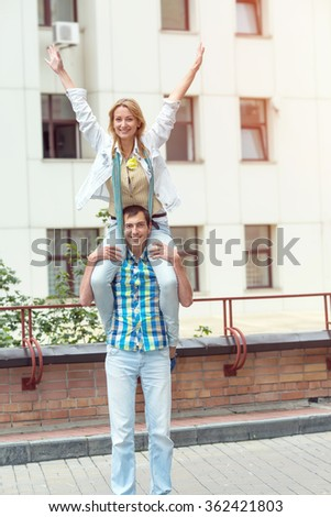 Happy loving couple. Young man and woman. Wings of love. Strong young man, carrying his girlfriend on shoulders while standing on city street. Happy young man and his girlfriend arms outstretched. - stock photo