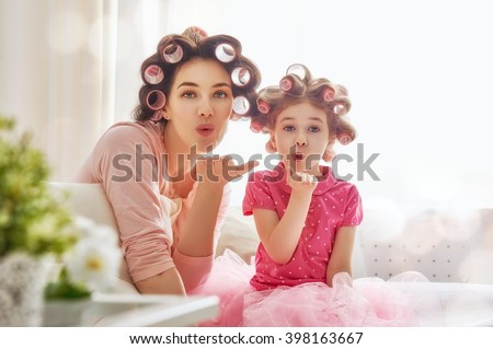 Happy loving family. Mother and daughter are doing hair and having fun. Mother and her child girl playing, kissing and hugging. - stock photo