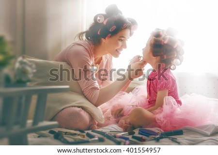 Happy loving family. Mother and daughter are doing hair and having fun. Mother putting lipstick on her daughter. - stock photo