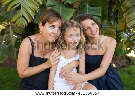 Happy loving family. Mother and her daughters children girls sitting on a background of palm trees - stock photo