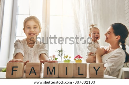 Happy loving family playing with blocks and having fun. Blocks have letters. Mother and her daughters lay out cubes and word family. - stock photo