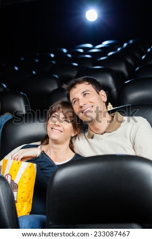 Happy loving mid adult couple watching film in movie theater - stock photo