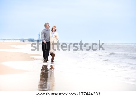 Happy loving middle aged couple walking on a beautiful beach in Holland - stock photo