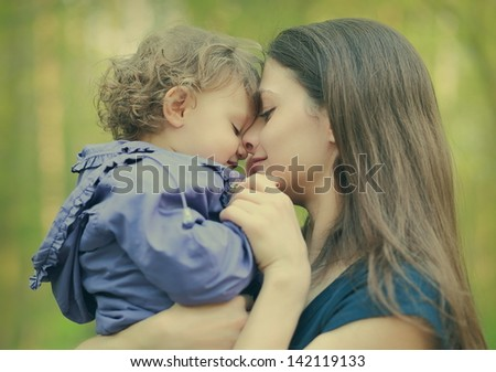 Happy loving mother and baby girl embracing outdoor summer background. Closeup portrait - stock photo