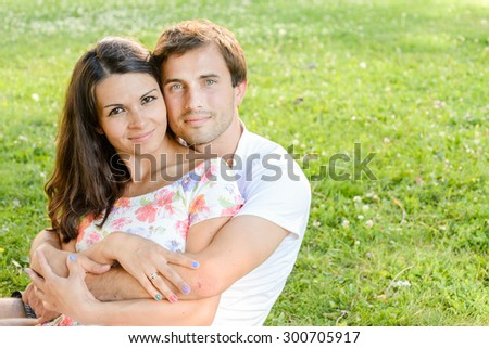 Happy loving pretty young couple outdoors having fun on sunny day. Handsome man and his pretty girlfriend posing outdoor, enjoying time together. Romance and love concept.  - stock photo