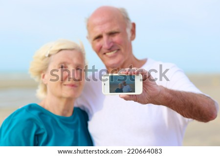 Happy loving senior couple enjoying vacation together having fun on the beach taking selfie photo using smartphone camera. Concept of active retirement and interaction with new technologies and trends - stock photo