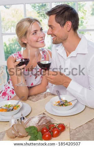 Happy loving young couple with wine glasses looking at each other at dining table at home - stock photo