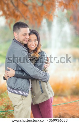 Happy loving young embracing while walking in a park - stock photo