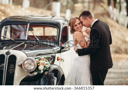 Happy luxury wedding couple kissing and embracing near retro with bouquet car in autumn - stock photo
