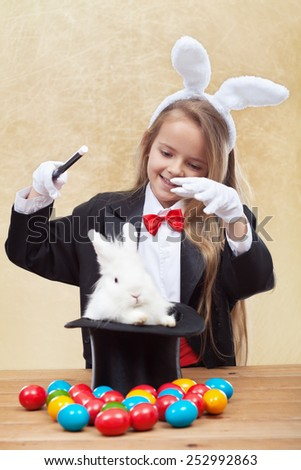 Happy magician girl conjuring up the easter bunny and colorful eggs - stock photo