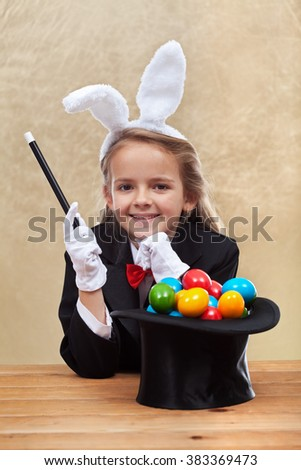 Happy magician girl making easter eggs with her super powers - on golden background - stock photo