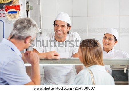Happy male and female butchers looking at customer in shop - stock photo