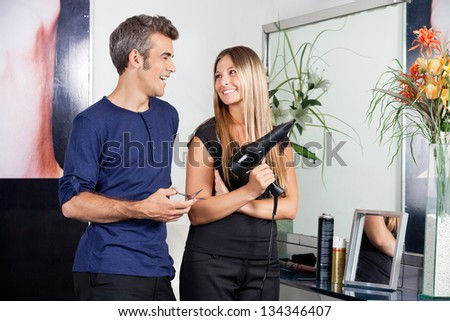 Happy male and female hairdressers looking at each other in salon - stock photo