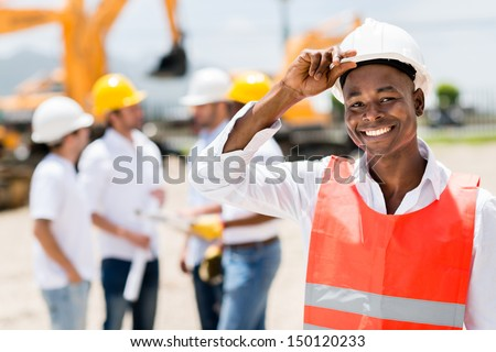 Happy male architect at a building site wearing a helmet  - stock photo