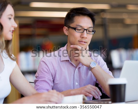 Happy male asian student working at the library - stock photo