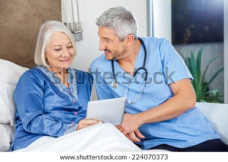 Happy male caretaker with senior woman using digital tablet in bedroom at nursing home - stock photo