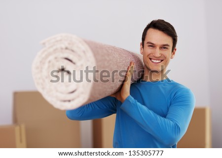 Happy male carrying a carpet in new home - stock photo