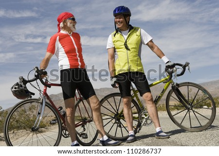 Happy male cyclists standing by their bicycles - stock photo