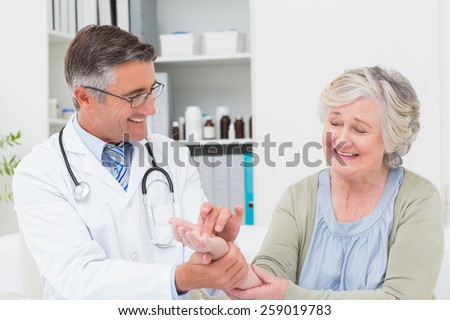 Happy male doctor examining patients hand at table in clinic - stock photo