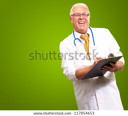 Happy Male Doctor Writing On Clipboard Isolated On Green Background - stock photo