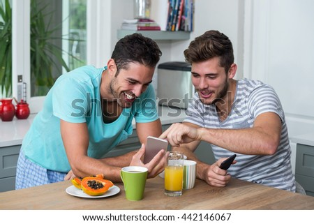 Happy male friends using phone while standing at table - stock photo