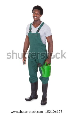 Happy Male Gardener Holding Watering Can And Pliers Over White Background - stock photo