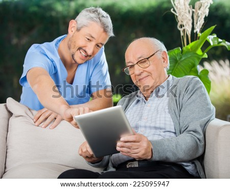 Happy male nurse helping senior man in using tablet computer at nursing home porch - stock photo