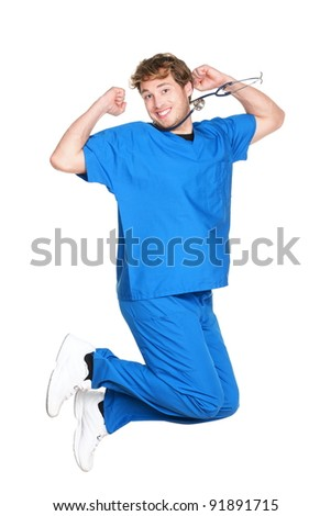 happy male nurse or doctor jumping in blue scrubs smiling excited. Young medical professional. Caucasian man in his twenties wearing stethoscope isolated on white background. - stock photo