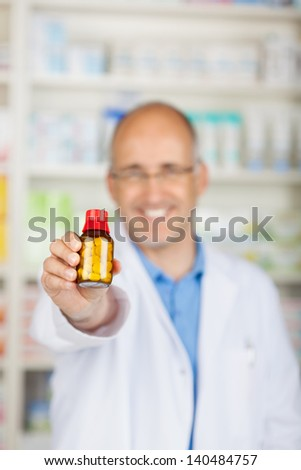 Happy male pharmacist holding medicine bottle in pharmacy - stock photo