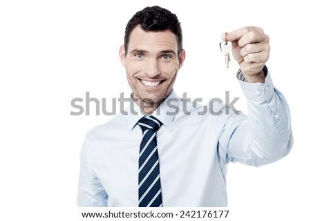 Happy male realtor showing new house keys - stock photo