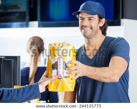 Happy male seller selling popcorn to man at cinema concession stand with colleague in background - stock photo
