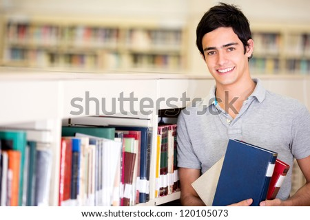 Happy male student holding books at the library - stock photo