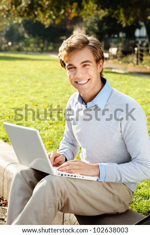 happy male student using laptop outdoors - stock photo
