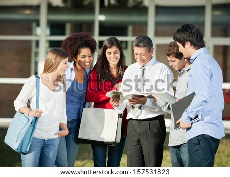Happy male teacher explaining lesson to students on college campus - stock photo