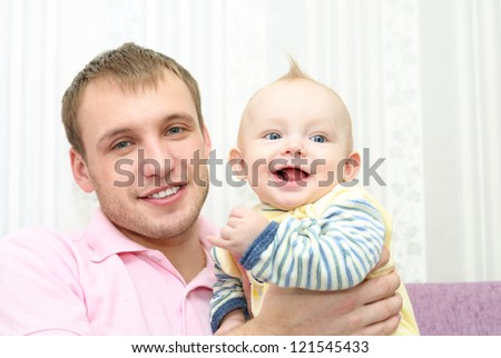 Happy man and baby boy   at home. Focus on the child - stock photo