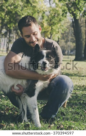 Happy man and his dog play in the park. Retro filter added. - stock photo