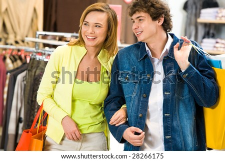 Happy man and his girlfriend with paperbags looking at something in the shopping mall - stock photo