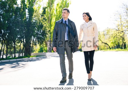 Happy man and smiling woman walking in park - stock photo