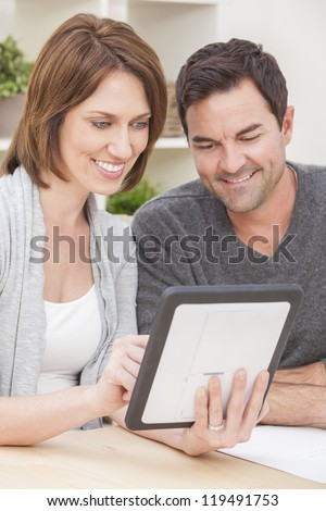 Happy man and woman couple in their thirties, sitting together at home by a table using a tablet computer - stock photo